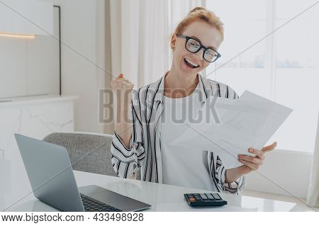 Overjoyed Excited Redhead Woman In Spectacles Exclaiming Yes With Happy Face Expression While Calcul