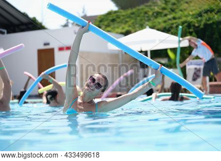 Attractive Woman Doing Exercises With Noodles Is Engaged In Aqua Aerobics