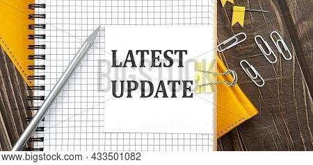 Latest Update Text On Sticker On The Notebook, Wooden Background