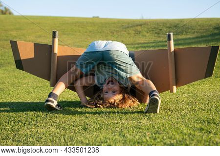 Funny Child Upside Down On Grass. Childhood Imagination, Kid Dream To Adventure Travel. Travel And V