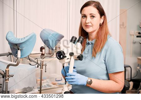 Portrait Woman Gynecologist Working In Gynecological Cabinet With Modern Equipment. Doctor In Blue S