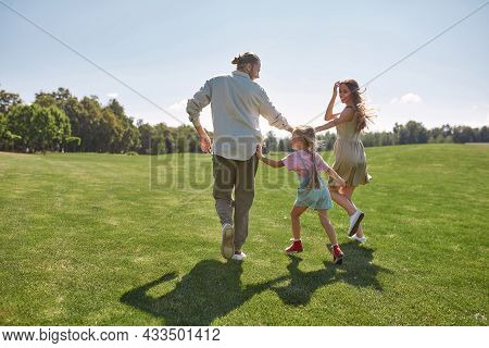 Active Little Girl Playing Together With Her Parents, Catching Them In Green Park On A Summer Day. C
