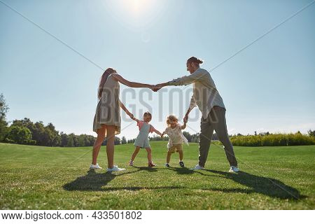 Happy Young Parents Spending Time Together, Holding Hands In Circle With Their Two Little Kids, Boy