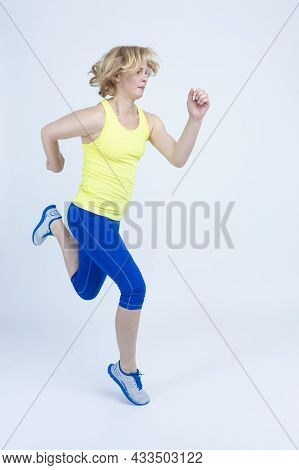Sportswoman Concepts. Running Mature Sportswoman During Active Jogging Training  Against White Backg