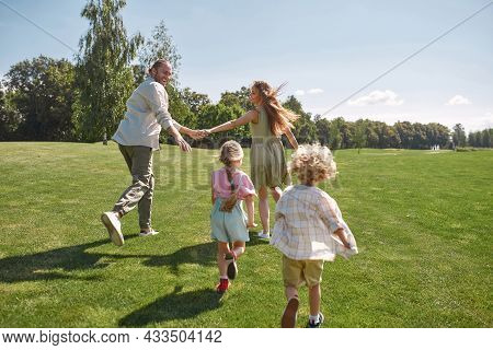 Joyful Parents Holding Hands, Running From Their Little Kids, Boy And Girl, Having Fun Together In G
