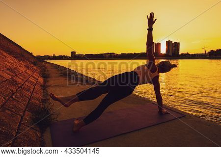 Woman Exercising Pilates On Sunny Day. Side Plank With Leg Kick Exercise.