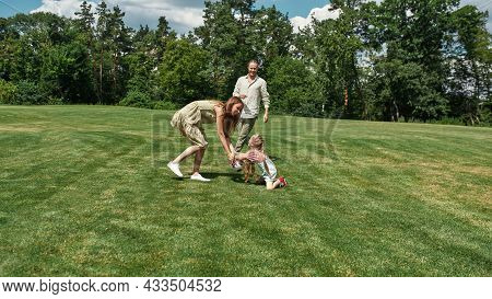 Happy Family Having Fun, Playing Football On The Grass Field In The Park On A Summer Day. Childhood,
