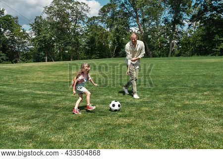 Active Young Father Playing Football Together With His Little Daughter On The Grass Field In The Par