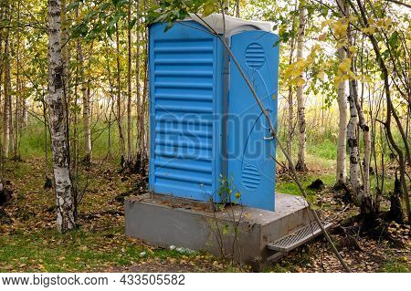Outdoor Chemical Toilet In The Park. Eco-friendly Bio Toilet In Nature. Blue Cabine Of Bio Toilet In