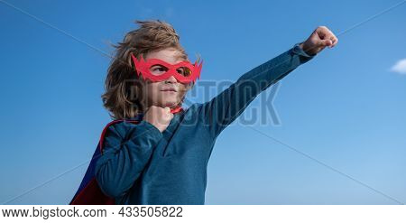 Seriuos Child Wearing A Superhero Costume. Super Hero Child Against Blue Summer Sky Background. Kid