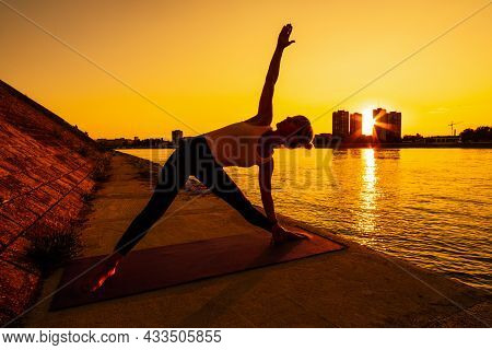 Young Woman Is Exercising Outdoor. She Is Practicing Yoga On Sunny Day. Trikonasana, Bikram Triangle