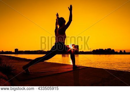 Young Woman Is Exercising Outdoor. She Is Practicing Yoga On Sunny Day. Virabhadrasana / Variation O