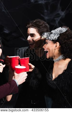 Excited African American Woman Clinking Plastic Cups With Friends Singing Karaoke On Halloween Party