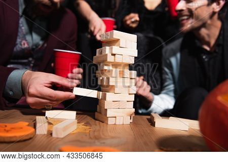 Partial View Of Blurred Friends Playing Wood Blocks Game During Halloween Party