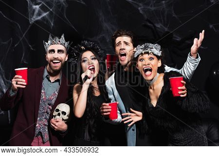 Cheerful Multicultural Friends In Halloween Makeup And Costumes Singing Karaoke On Black