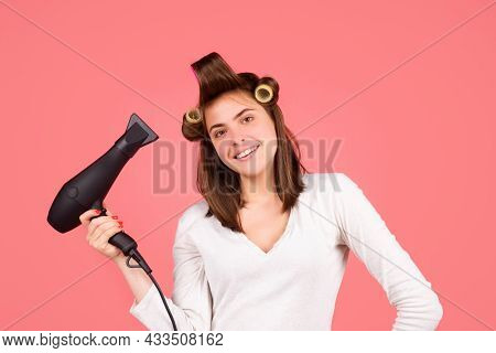 Smiling Woman With Hair Dryer. Beautiful Happy Girl With Straight Hair And Rollers Drying Hair With