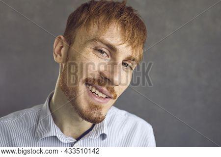 Closeup Studio Portrait Of Happy Confident Redhead Man Looking At Camera And Smirking
