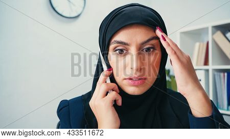 Stunned Muslim Businesswoman In Hijab Talking On Cellphone In Office