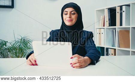 Cheerful Arabian Woman In Hijab Looking At Digital Tablet In Office