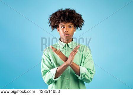 Serious Black Teen Guy Showing Stop Or No Gesture, Crossing Hands, Dislike Or Deny Something, Blue B