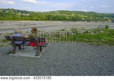 Two Elder Women In Medical Masks Sitting On The Bench, Enjoying The River View And Talking. Active T