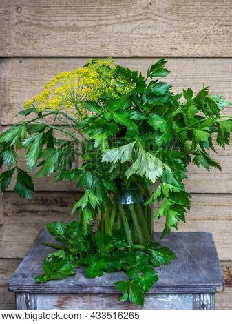 Leafy Celery In A Tall Glass Jar On A Wooden Stool On The Porch Of A Country House