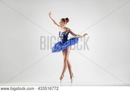 Attractive Ballerina With Bun Collected Hair Wearing Blue Dress And Pointe Shoes Performing In White