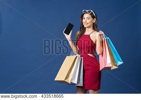 Happy Young Asian Woman Using Mobile Phone For Online Shopping On Blue Color Background, Cashless Pa