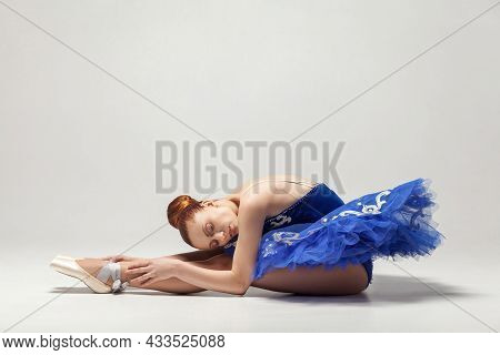 Beautiful Ballerina With Bun Collected Hair In Dress And Pointe Shoes Stretching Isolated On White B