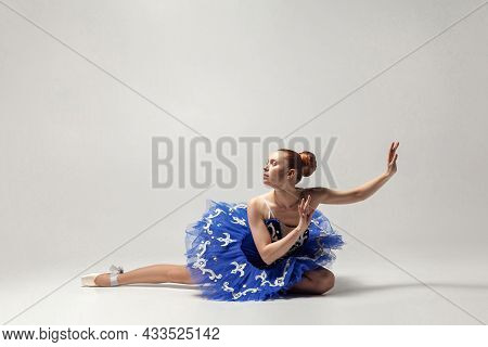 Attractive Ballerina With Bun Collected Hair Wearing Blue Dress And Pointe Shoes Graceful Sitting On