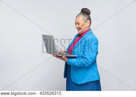Aged Woman Standing And Holding Laptop And Looking At Screen With Satisfied Face. Grandmother In Lig