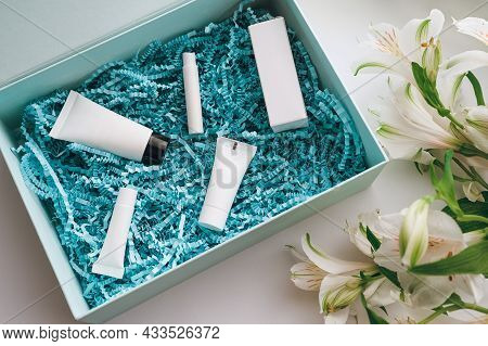 Package With Cosmetics: Mask, Moisturizer, Serum, Perfume, Eye Cream In Blue Wrapping Paper Shavings