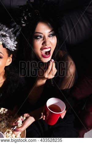 Asian Woman With Scary Grimace Eating Popcorn During Halloween Party