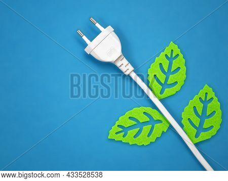 White Power Plug With Green Leaves Isolated On Blue Background, Concept Image Of Green Ecological En