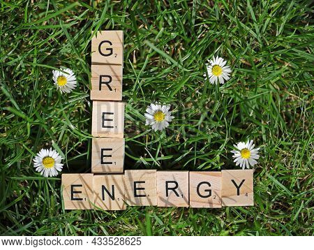 Top View Of The Words Green Energy, Written With Wooden Blocks In The Grass Between Daisies, Eco Con