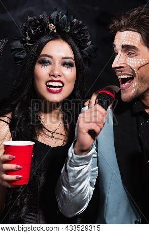 Happy Asian Woman Holding Plastic Cup Near Man In Halloween Makeup Singing Karaoke On Black