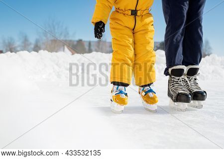 A Girl In Overalls Learns To Skate With Her Dad On A Sunny Day At The City Public Ice Rink. The Man