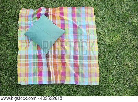 Checkered Colorful Blanket With Pillow On Green Grass Top View. Checked Picnic Towel. Summertime Des