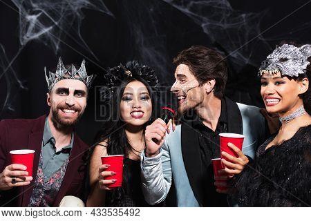 Man In Halloween Makeup Singing Karaoke Near Multiethnic Friends With Plastic Cups On Black