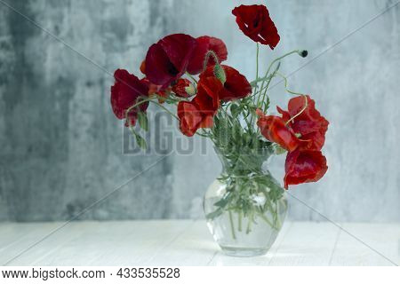 Bouquet Of Red Poppy Flowers In Glass Vase.