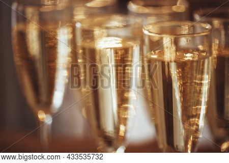 Transparent Wineglasses With Champagne Placed On Blurred Background Of Bright Illumination During Pa