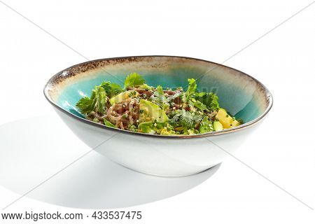 Healthy pasta soba with green vegetables. Vegetarian dish - soba with zucchini, broccoli and green pea on ceramic bowl. Veggie food handmade bowl isolated on white background. Plant based bowl dining