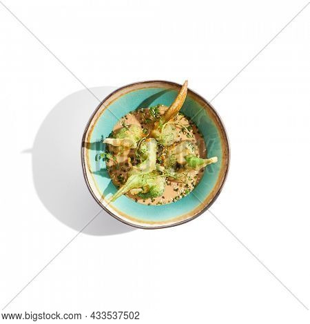 Broccoli and cauliflower roasted with peanut sauce on white background. Healthy organic vegan food - oven cabbage. Fresh healthy food baked broccoli. Vegetarian dish. Plant - based eating. Alt-meat