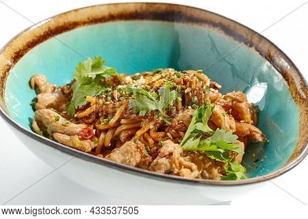Japanese soba with chicken cooked on wok in asian style on white background. Noodle with chicken in ceramic bowl. Indonesian wok with soba noodles. Spicy thai dish with meat and udon