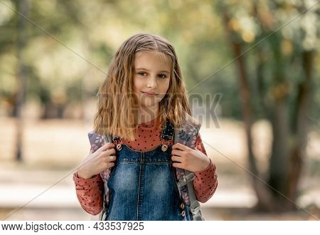 Preteen school girl with backpack closeup portrait outdoors. Pretty pupil female kid after education class in autumn park