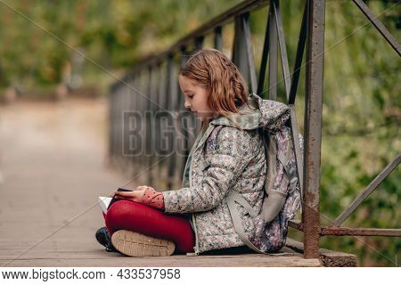 Preteen school girl with backpack sitting on ground and reading book outdoors. Sweet pupil female kid studying in autumn park