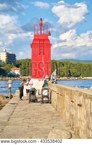 Krk, Croatia - August 05, 2021: Holidaymakers On The Promenade By The Lighthouse In The Town Of Krk