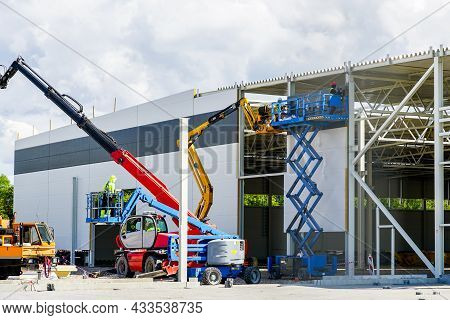 A Sandwich Panel Wall Is Mounted With The Help Of A Modern Telescopic Crane And Scissor Lifts