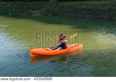 8 Year Old Brazilian Child Learning To Use A Kayak In A Small River.d