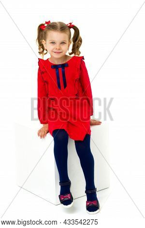 Portrait Of Beautiful Blonde Girl In Red Dress. Adorable Little Girl With Ponytails Wearing Nice Dre